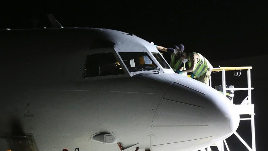 In this photo taken March 30, 2014, ground crew repair a window on a Royal Australian Air Force P-3 Orion at RAAF Base Pearce after the aircraft returns from the search for the missing Malaysia Airlines Flight 370 in Perth, Australia. The ground crews typically work on the tarmac through the night so the planes are ready to fly again by daylight, as the international effort to find some trace of the missing jetliner continues. (AP Photo/Rob Griffith)