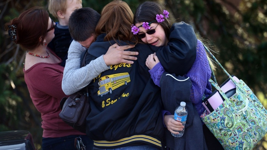 Parents and students embrace near Franklin Regional High School, April 9, 2014, in Murrysville, Pa.