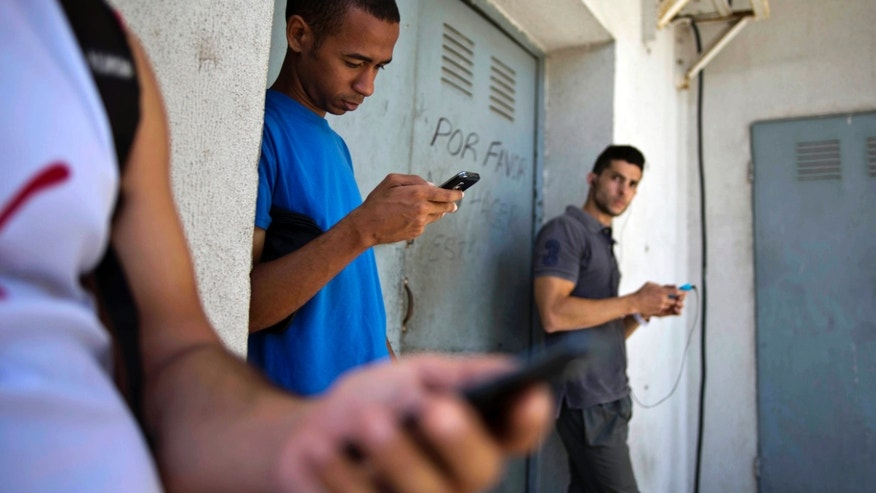 Students looking for a Internet signal for their smart phones in Havana, Cuba, Tuesday, April 1, 2014.