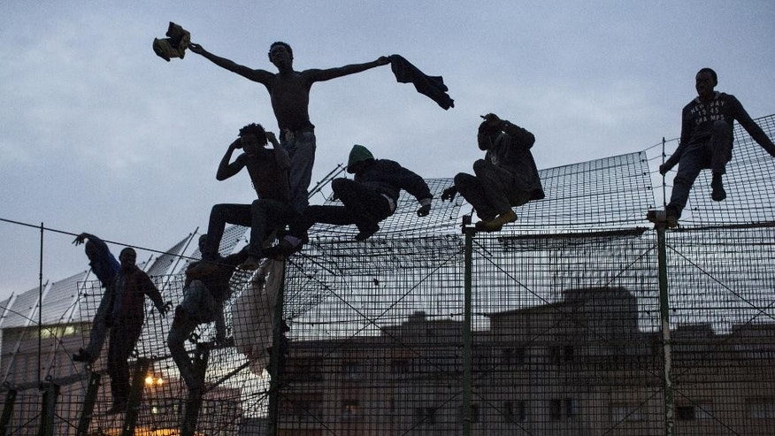 In this photo taken on Friday March 28, 2014,  Sub-Saharan migrants react  on top of a metallic fence that divides Morocco and the Spanish enclave of Melilla. For more than seven hours, some 27 sub-Saharan African migrants sat atop the 20-foot fence dividing Europe from Africa at Morocco's border with the Spanish enclave of Melilla refusing to come down. Buffeted by the chilly winds whipping along the epic cliffs of Africa's Mediterranean coast, the men nursed their bloody feet and pleaded in broken French for the Red Cross. (AP Photo/Santi Palacios)