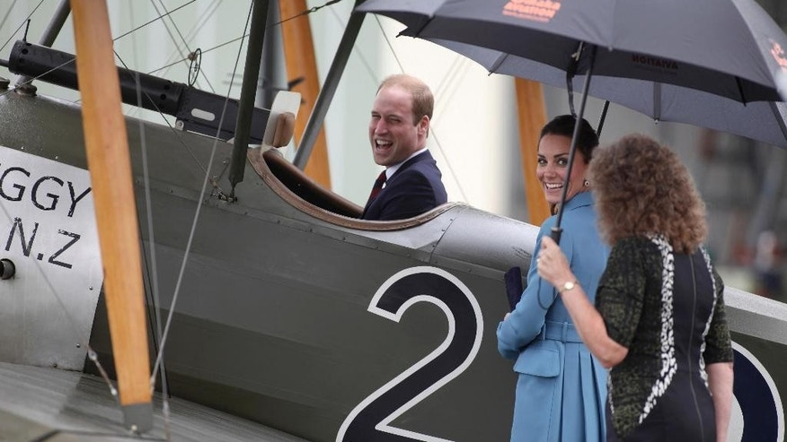 Britain's Prince William, left, sits in a classic Sopwith Pup as he and his wife Kate, the Duchess of Cambridge, center, tour the Omaka Aviation Heritage Centre in Blenheim, New Zealand, Thursday, April 10, 2014. (AP Photo/Tim Cuff, Pool)