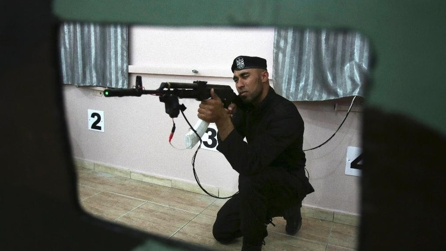 "Palestinian security officer Ahed Abu Shabban, 23, aims an electronically-modified AK-47 rifle at the headquarters of the security training department of the Hamas interior ministry in Gaza City, in the northern Gaza Strip on Thursday, April 10, 2014. Adnan Abu Amer, an expert on Palestinian militant groups at Gaza's Al Ummah University, says the prices of some weapons have nearly doubled in recent months, and the price of ammunition has tripled. ""The most significant result of the tunnel demolitions has been the scarcity of weapons, ammunition and explosives,"" he says. (AP Photo/Adel Hana)"