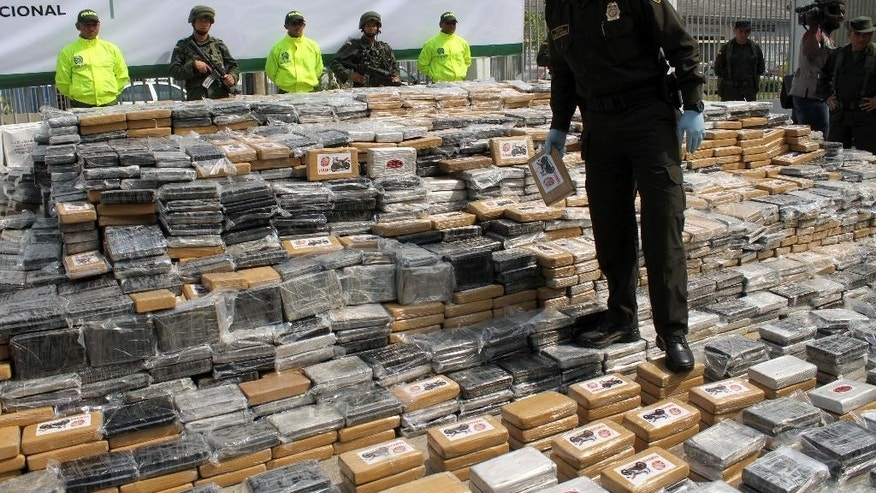 Colombia National Police Chief, Gen. Rodolfo Palomino walks on seized packages of cocaine displayed for the press at a police base in the Caribbean seaport of Cartagena, Colombia, Thursday, April 10, 2014. Police say they seized about 7 tons of cocaine Wednesday in a container bound for the Netherlands' port of Rotterdam. (AP Photo/Felipe Caicedo)