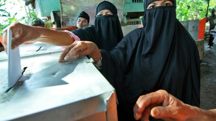 Members of An-Nadzir Muslim sect cast their ballots at a polling station during the parliamentary election in Gowa, South Sulawesi, Indonesia, Wednesday, April 9, 2014.   Polls opened Wednesday for nearly 187 million Indonesians eligible to vote in single-day legislative elections, a huge feat in the still-young democracy that's expected to help clear the path for the country's next president. (AP Photo/Masyudi S. Firmansyah)