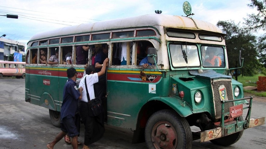 In this Aug. 22, 2012 photo, passengers get into a slowly moving Chevrolet bus in Yangon, Myanmar. These old Chevys,  built on the Canadian made military personnel carriers that were left behind after Work war 11, were sent to the scrap heap at the end of 2012. Because of the abysmal state of public transport in Yangon, a city of 5 million, those who can afford to drive, do. Those who can't cram into ancient buses perched precariously on huge tires or hitch rides on pickups outfitted with benches and makeshift roofs. (AP Photo/Khin Maung Win)