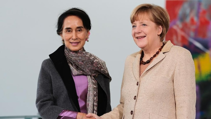 German Chancellor Angela Merkel, right, welcomes Myanmar Opposition Leader Aung San Suu Kyi, center, for a meeting at the chancellery in Berlin, Germany, Thursday, April 10, 2014. (AP Photo/Markus Schreiber)