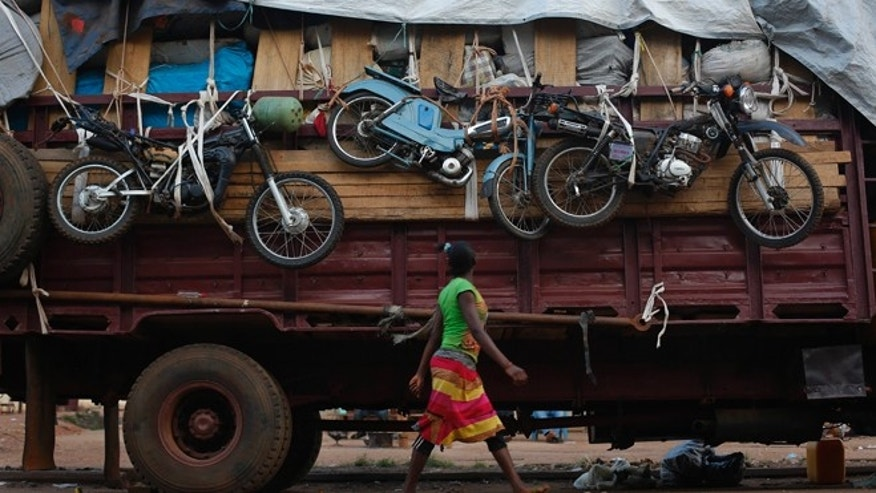 Apr. 9, 2014: A woman walks past a truck waiting to leave for Chad loaded with goods belonging to Muslim residents of the PK5 district of Bangui, Central African Republic.