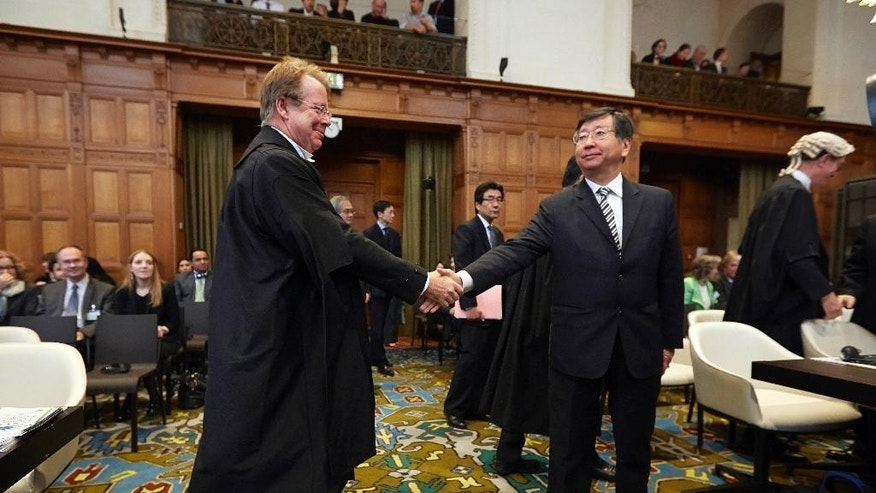 FILE - In this Monday, March 31, 2014 file photo, Japanese Ambassador to the Netherlands, and Chief Negotiator, Koji Tsuruoka, center, shakes hand with General Counsel of Australia Bill Campbell before the International Court of Justice to deliver its verdict in The Hague, Netherlands. The international court ruling against Japanese whaling last week may have given the government a convenient political out. The Antarctic program was nearly bankrupt, but if the government had overhauled it on its own, it would have incurred the wrath of a strong anti-whaling lobby, and could have been criticized for caving in to foreign anti-whaling activists. Now officials can say the court forced their hand. (AP Photo/Phil Nijhuis, File)