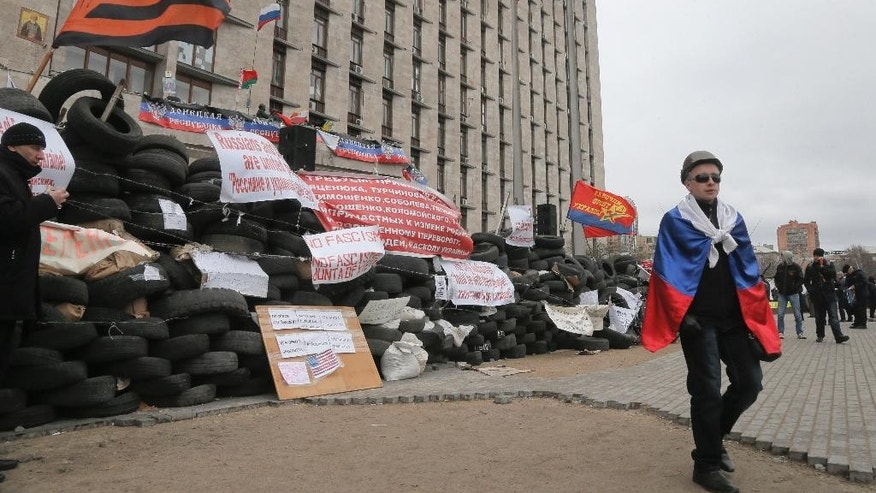 A pro-Russian  activist with a Russian flag pass by a barricade at a regional administration building that they had seized earlier in Donetsk, Ukraine, in Donetsk, Ukraine,  Friday, April 11, 2014. Ukraine's prime minister on Friday told leaders in the country's restive east that he is committed to allowing regions to have more powers. Yatsenyuk Friday morning flew into Donetsk, where pro-Russian separatists are occupying the regional administration building and calling for a referendum that could prefigure seeking annexation by Russia. (AP Photo/Efrem Lukatsky)