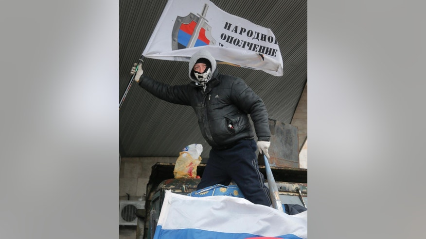 A masked pro-Russian activist holds up a flag on top of a barricade as he guards a regional administration building that they had seized earlier in Donetsk, Ukraine, Friday, April 11, 2014. The text on the flag reads: 'Militia of Donbass'. Ukraine's prime minister on Friday told leaders in the country's restive east that he is committed to allowing regions to have more powers. Yatsenyuk Friday morning flew into Donetsk, where pro-Russian separatists are occupying the regional administration building and calling for a referendum that could prefigure seeking annexation by Russia. (AP Photo/Efrem Lukatsky)