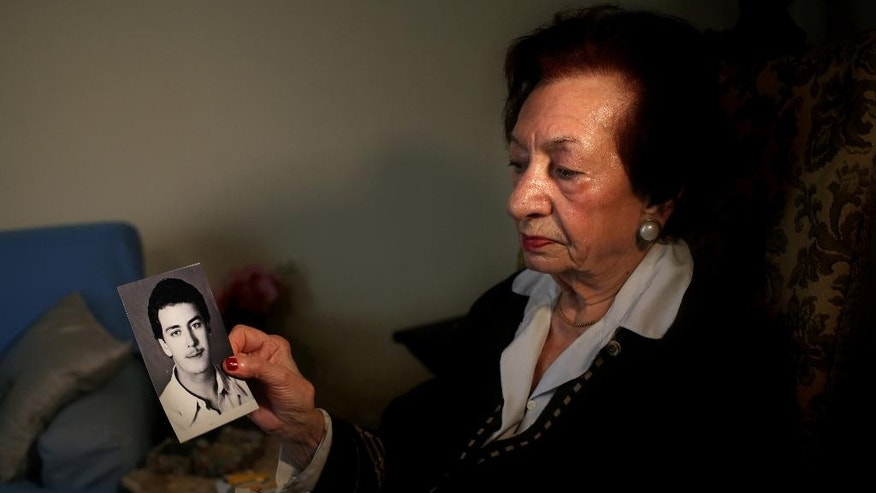 In this Thursday April 10, 2014 photo, Lebanese Mary Mansourati, 82, whose son Dani went missing in Syria in 1992 at the age of 30, show his portrait during an interview with the Associated Press at her house, in Beirut, Lebanon. Dani is among an estimated 17,000 Lebanese still missing from the time of Lebanon's civil war or the years of Syrian domination that followed. Syria's civil war has added new urgency to the plight of their families, many of whom are convinced their loved ones are still alive and held in Syrian prisons, at risk of being lost or killed in the country's mayhem. (AP Photo/Hussein Malla)