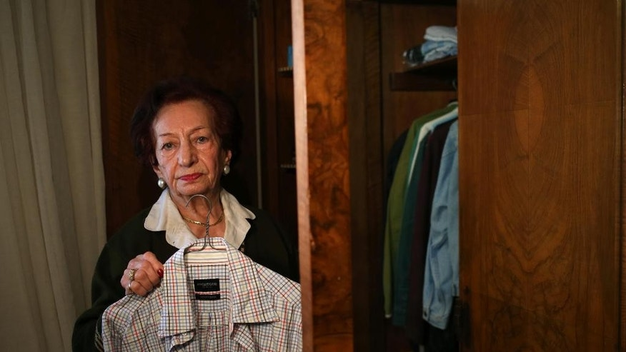 In this Thursday April 10, 2014 photo, Lebanese Mary Mansourati, 82, whose son Dani went missing in Syria in 1992 on the age of 30, shows one of his shirts from his bedroom cupboard, during an interview with the Associated Press at her house, in Beirut, Lebanon. Dani is among an estimated 17,000 Lebanese still missing from the time of Lebanon's civil war or the years of Syrian domination that followed. Syria's civil war has added new urgency to the plight of their families, many of whom are convinced their loved ones are still alive and held in Syrian prisons, at risk of being lost or killed in the country's mayhem. (AP Photo/Hussein Malla)