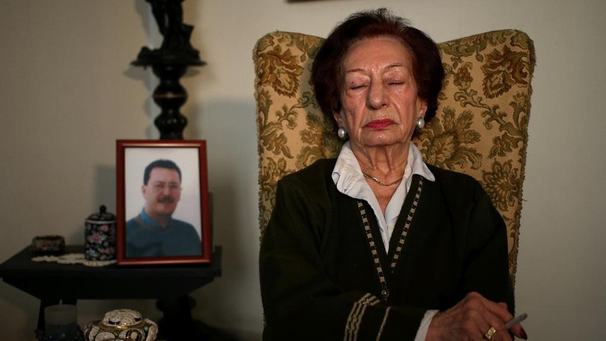 In this Thursday April 10, 2014 photo, Lebanese Mary Mansourati, 82, reflects on her son Dani who went missing in Syria in 1992 at the age of 30, his portrait seen at left, as she speaks during an interview with the Associated Press at her house, in Beirut, Lebanon. Dani is among an estimated 17,000 Lebanese still missing from the time of Lebanon's civil war or the years of Syrian domination that followed. Syria's civil war has added new urgency to the plight of their families, many of whom are convinced their loved ones are still alive and held in Syrian prisons, at risk of being lost or killed in the country's mayhem. (AP Photo/Hussein Malla) (AP Photo/Hussein Malla)