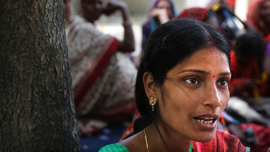 In this March 31, 2014 photo, Chaya Kumari, a field worker with a nongovernmental organization, speaks to village women in Sarai village on the outskirts of Varanasi, India. Women form more than 49 percent of India's 814 million voters, but many of them, especially in rural India, feel their concerns are not taken seriously by political parties, and that they take a back seat to men in everything from health care to education to legal protection. (AP Photo/Manish Swarup)