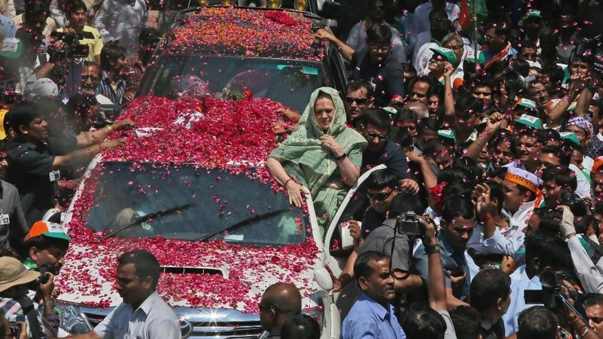 In this April 2, 2014 photo, chairperson of India's ruling United Progressive Alliance and Congress party President Sonia Gandhi, center, is welcomed with flowers as she arrives to file her nomination papers for the general elections, in Rae Bareli, India. Women form more than 49 percent of India's 814 million voters, but many of them, especially in rural India, feel their concerns are not taken seriously by political parties, and that they take a back seat to men in everything from health care to education to legal protection. (AP Photo/Manish Swarup)