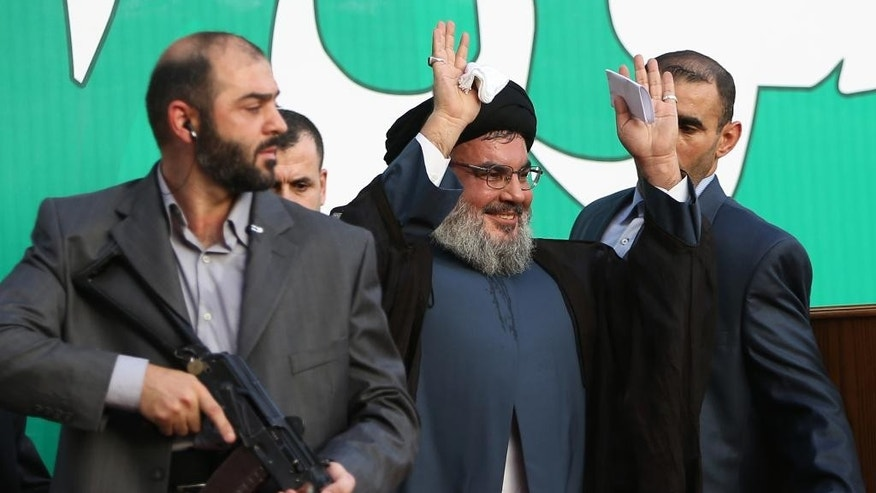 FILE - In this Monday, Sept 17, 2012 file photo, Hezbollah leader Sheik Hassan Nasrallah, center, escorted by his bodyguards, waves to a crowd of tens of thousands of supporters during a rally denouncing an anti-Islam film that has provoked a week of unrest in Muslim countries worldwide, in the southern suburb of Beirut, Lebanon. The Shiite group has sent hundreds of its fighters into Syria to shore up President Bashar Assad's overstretched troops, helping them gain ground around the capital, Damascus, and near the Lebanese border. But with its own casualties mounting in a civil war that activists say has killed more than 150,000 people in three years, officials say Hezbollah has turned to a variety of new tactics - including complicated commando operations - to hunt down rebels and opposition commanders. (AP Photo/Hussein Malla, File)