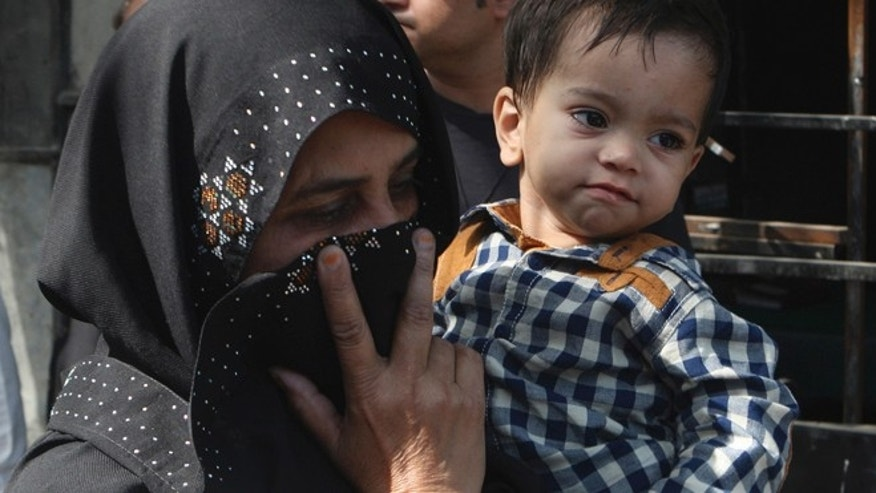 APRIL 12: An unidentified family member holds a nine-month-old boy, trying to avoid media as they leave after the boy's court appearance in Lahore, Pakistan.