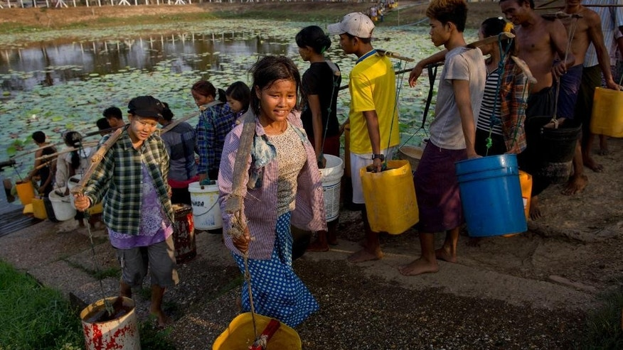 In this April 2, 2014 photo, residents of Dala, carry repurposed plastic containers filled with drinking water fetched from a natural water pond in the suburbs of Yangon, Myanmar. During the annual dry season in April and May, residents pay 10 kyat, or 10 U.S. cents for each bucket of water and walk up to five kilometers (three miles) carrying the buckets for their families in this improvised neighborhood. (AP Photo/Gemunu Amarasinghe)