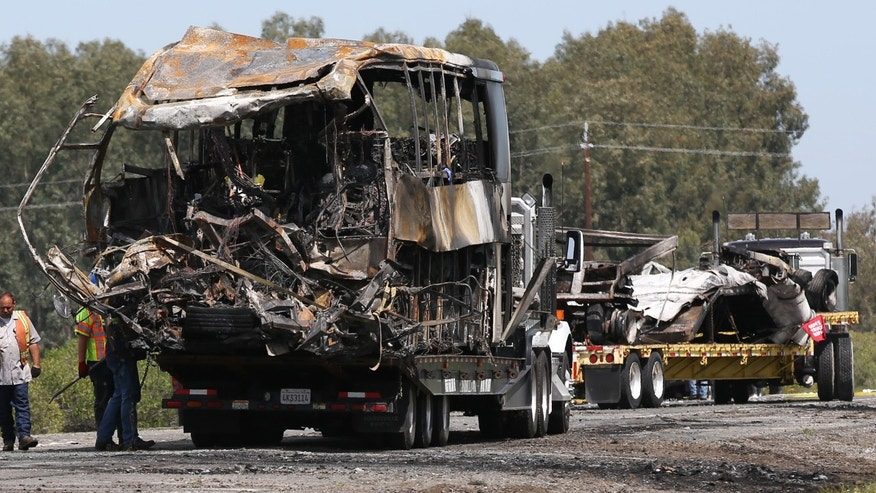 ORLAND, CA - APRIL 11: The remains of a FedEx truck, right, and bus, left, involved in Thursday's deadly crash are seen on trucks at the scene of the accident on April 11, 2014  in Orland, California. Ten people were killed and dozens injured, including four still in critical condition, after a FedEx truck collided with a bus of high school students on Interstate 5 yesterday. The students were on their way to visit Humboldt State University in Northern California. (Photo by Elijah Nouvelage/Getty Images)