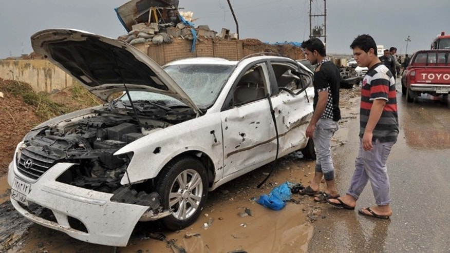 April 13, 2014: Iraq civilians inspect the site of a suicide car bombing in the northern town of Dibis, near the city of Kirkuk, 180 miles north of Baghdad, Iraq.