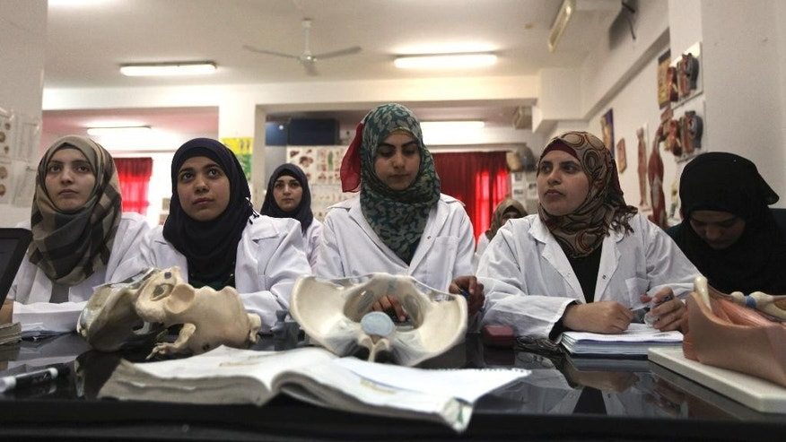 In this Thursday, April 10, 2014 photo, Palestinian students attend a lesson in the Faculty of Medicine at the Al-Quds University in the West Bank village of Abu Dis, near Jerusalem. Dozens of Palestinian doctors who graduated from Al-Quds University, a school that has a foothold in east Jerusalem, are caught in the political battle between Israel and the Palestinians over the city's eastern sector. Israel has refused to recognize the university's graduates -- a move that could amount to acknowledging the Palestinian claims to east Jerusalem as their capital. (AP Photo/Majdi Mohammed)