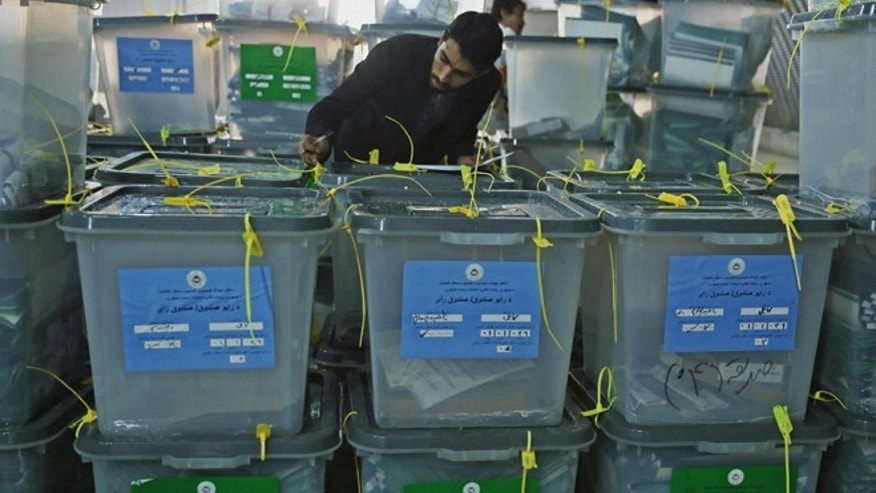 April 6, 2014: An Afghan elections worker notes the serial numbers of ballot boxes at a warehouse Independent Elections Commission in Kabul, Afghanistan.