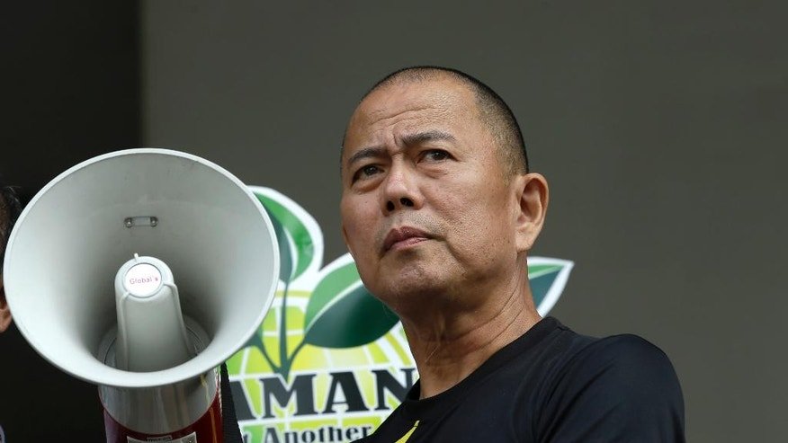 "In this Feb. 20, 2014 photo, Roman Catholic priest Father Robert Reyes holds a megaphone for a speaker to protest the privatization of a government hospital that will pave the way for the construction of shopping malls in Quezon city northeast of Manila, Philippines. For more than 30 years, Reyes, dubbed the ""running priest"" by the local media, has been a constant critic of corruption in the Philippines and often times the church itself, which he charges has abandoned its obligation to help the poor and sided with those in power in Asia's largest Roman Catholic nation. (AP Photo/Bullit Marquez)"