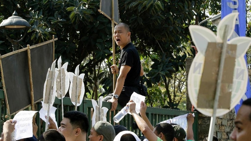 "In this Feb. 20, 2014 photo, Roman Catholic priest Father Robert Reyes sits on the gates of the National Housing Authority after jogging with supporters to protest the demolition of an informal settlers community that will pave the way for the construction of shopping malls in Quezon city northeast of Manila, Philippines. For more than 30 years, Reyes, dubbed the ""running priest"" by the local media, has been a constant critic of corruption in the Philippines and often times the church itself, which he charges has abandoned its obligation to help the poor and sided with those in power in Asia's largest Roman Catholic nation. (AP Photo/Bullit Marquez)"