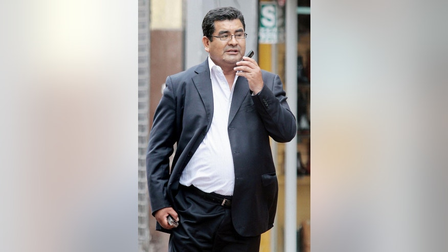 """In this Nov. 26, 2013 photo, Ancash Gov. Cesar Alvarez talks on his cell phone in Lima, Peru. Alvarez ran a """"mini-dictatorship"""" in a state plagued by political murder where the courts and prosecutor's office were """"taken over by criminals,"""" Peru's anti-corruption prosecutor alleges. A judge has barred him from leaving the country while more than 100 shelved corruption cases are revived. (AP Photo/Edwin Julca)"""