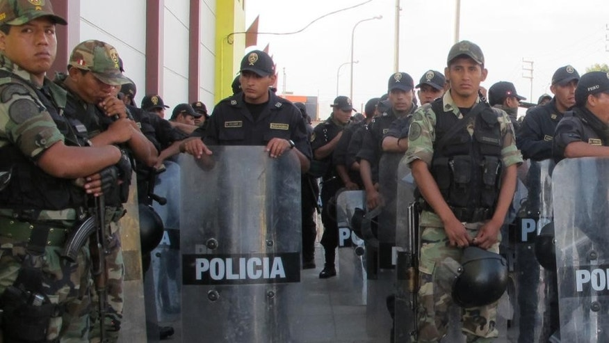In this April 7, 2014 photo, police stand guard outside the auditorium in Chimbote, Peru. Inside, Congress' investigations committee had just heard from an angry public that has long been living in fear accuse Gov. Cesar Alvarez of running mining-rich Ancash state as his personal fiefdom. At the hearing, Peru's chief prosecutor, comptroller and the committee chair all apologized for failing to prevent a political murder whose victim's longstanding campaign to expose wrongdoing in Ancash had been all but ignored in the capital. (AP Photo/Frank Bajak)