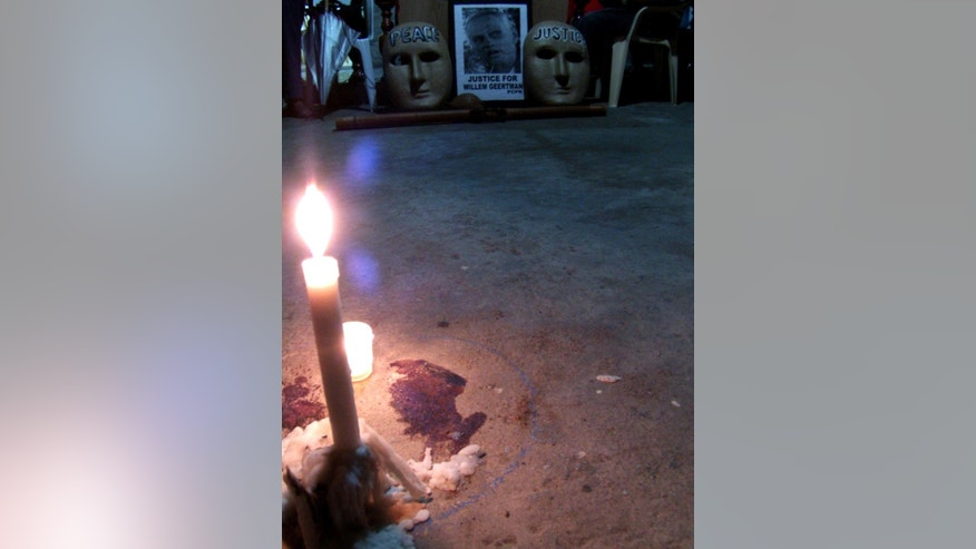 FILE - In this July 6, 2012 file photo, candles are lit at the very spot where Dutch environmental activist Wilhem Geertman, a former religious missionary who helped poor farmers affected by illegal logging and mining, was killed allegedly in a robbery attempt in San Fernando city, Pampanga province, north of Manila, Philippines. A survey released Tuesday, April 15, 2014 - the first comprehensive one of its kind – says that only 10 killers of 908 environmental activists slain around the world over the past decade have been convicted. (AP Photo/Sylwyn Sheen Alba, File)