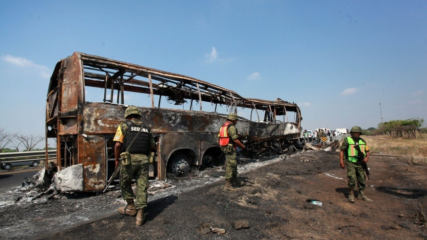 April 13, 2014 - Soldiers guard the site where a passenger bus slammed into a broken-down truck and burst into flames near the town of Ciudad Isla in the Gulf state of Veracruz, Mexico. Dozens of people traveling on the bus to Mexico City burned to death inside the bus.
