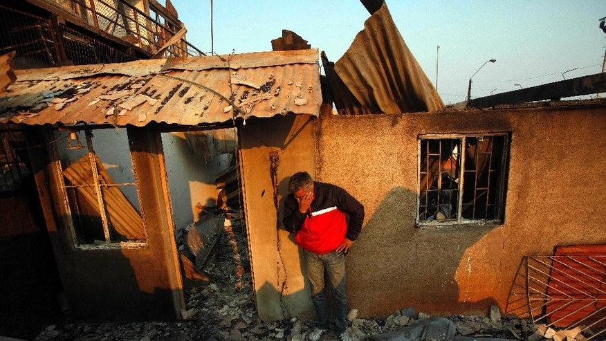 A man cries next to the remains of his house after a forest fire destroyed it in Valparaiso, Sunday, April 13, 2014. A raging fire leaped from hilltop to hilltop in this port city, killing at least 11 people and destroying more than 500 homes. More than 10,000 people were evacuated. (AP Photo/Luis Hidalgo)
