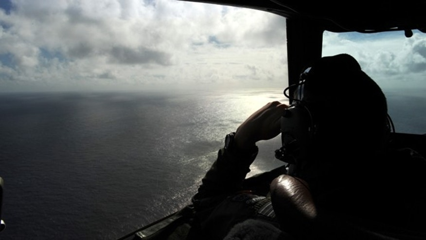 April 13, 2014: In this photo taken from the Royal New Zealand air force (RNZAF) P-3K2-Orion aircraft, pilot and aircraft captain, Flight Lieutenant Timothy McAlevey looks out of a window while searching for debris from missing Malaysia Airlines Flight 370, in the Indian Ocean off the coast of western Australia. (AP Photo/Greg Wood, Pool)