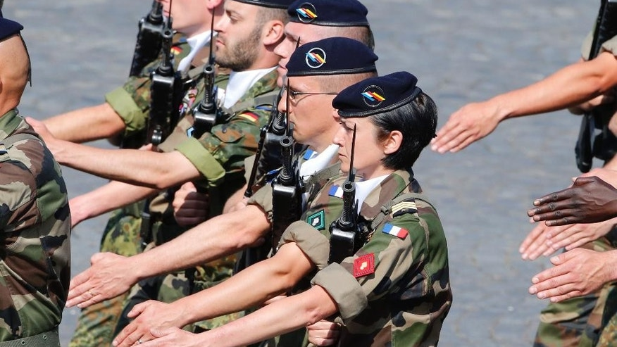 "FILE - In this July 14, 2013 file photo, a French female soldier, center, parades with a group of French and German soldiers during the Bastille Day parade in Paris. France claims great success in ""feminizing"" its military, with among the world's highest percentages of women in uniform. What it hasn't done is work to prevent sexual assault once they get there. The defense minister on Tuesday April 15, 2014 announced the first plan to address the problem and inflict harsher punishments on those found guilty. (AP Photo/Francois Mori, File)"