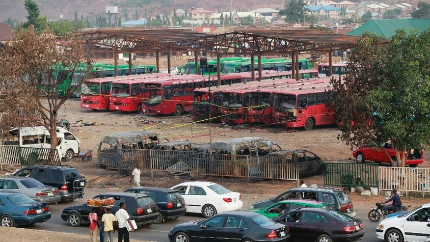 April 15, 2014: Cars drive past as onlookers inspect the scene of an explosion at a bus park in Abuja, Nigeria.