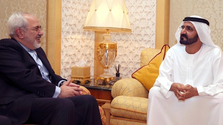 In this image released by the Emirates News Agency, WAM, Iranian Foreign Minister Mohamad Javad Zarif, left, meets with Sheikh Mohammed bin Rashid Al Maktoum, UAE Prime Minister and ruler of Dubai to discuss bilateral relations and regional developments, in Dubai, United Arab Emirates, Tuesday, April 15, 2014. (AP Photo/ WAM )