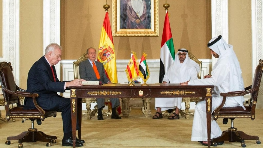 In this image released by the Emirates News Agency, WAM, Sheikh Abdullah bin Zayed Al Nahyan, Minister of Foreign Affairs, 1st right, and Jose Garcia-Margalo, Minister of Foreign Affairs and Cooperation of Spain, left, sign a memorandum of understanding for cultural cooperation between the UAE and Spain as Sheikh Mohamed bin Zayed Al Nahyan, Crown Prince of Abu Dhabi and Deputy Supreme Commander of the UAE Armed Forces, 2nd right, and Juan Carlos, King of Spain are seen, on the side lines of the UAE - Spain Economic Forum. (AP Photo/Ryan Carter - Crown Prince Court - Abu Dhabi )
