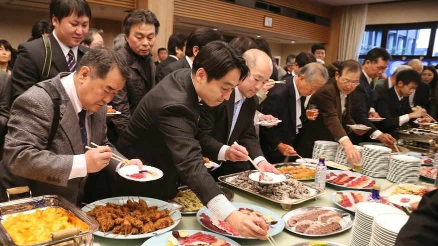 Supporters of Japan's whaling gather around the table for buffet during the 26th whale meat tasting event in Tokyo Tuesday, April 15, 2014. Hundreds of Japanese pro-whaling officials, lawmakers and lobby groups vowed to protect whale hunts despite the world court ruling that ordered the country's Antarctic research culls must be stopped. (AP Photo/Koji Sasahara)