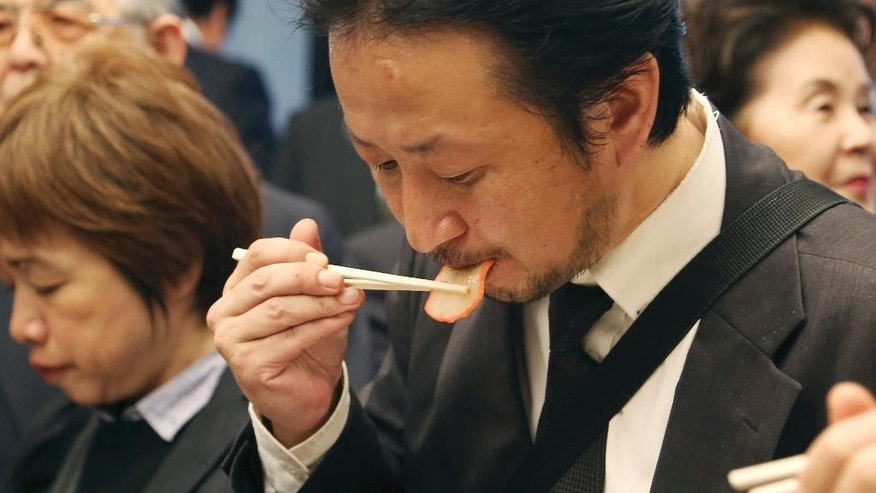 A supporter of Japan's whaling eats a slice of whale meat during the 26th whale meat tasting event in Tokyo Tuesday, April 15, 2014. Hundreds of Japanese pro-whaling officials, lawmakers and lobby groups vowed to protect whale hunts despite the world court ruling that ordered the country's Antarctic research culls must be stopped. (AP Photo/Koji Sasahara)