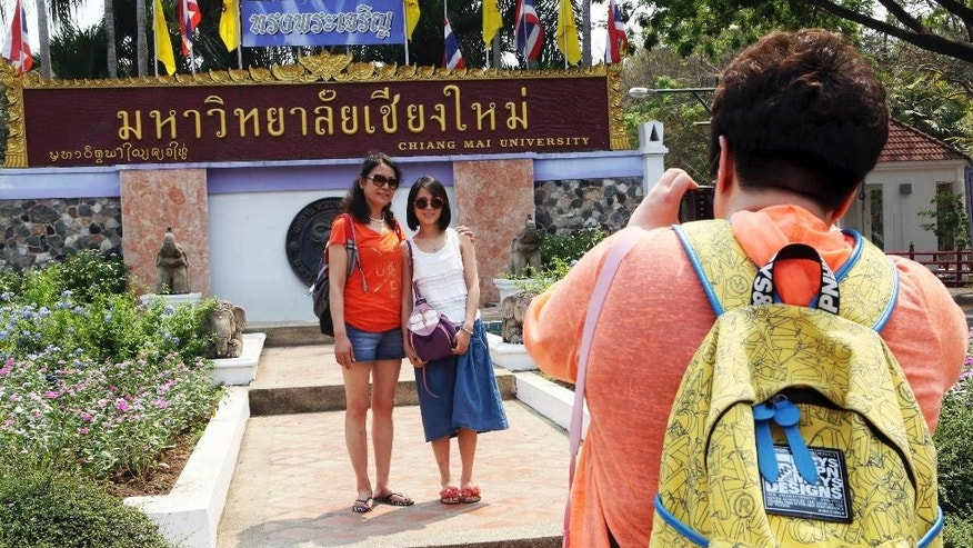 "In this March 30, 2014 photo, Chinese tourists pose for a photograph at the main entrance to Chiang Mai University in Chiang Mai province, northern Thailand. The bucolic, once laid-back campus of one of Thailand's top universities is under a security clampdown. Not against a terrorist threat, but against Chinese tourists. Thousands have clambered aboard student buses at the university, made a mess in cafeterias and sneaked into classes to attend lectures. Someone even pitched a tent by a picturesque lake. The reason: ""Lost in Thailand,"" 2012 slapstick comedy partly shot on campus that is China's highest-grossing homegrown movie ever. (AP Photo/Apichart Weerawong)"