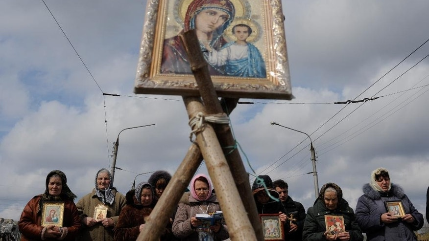 Women pray for peace near the Ukrainian regional administration building that was seized by pro-Russian activists in the eastern Ukrainian town of Slovyansk,  Ukraine, Monday, April 14, 2014. Over the past 10 days, more than a dozen government buildings have been seized by angry mobs in eastern Ukraine. In several cases, assaults have been led by automatic rifle-toting men in military fatigues claiming to be seeking autonomy for the Russian-speaking east. (AP Photo/Evgeniy Maloletka)