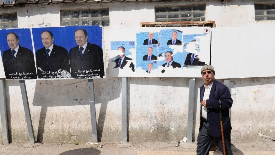 A man walks past electoral posters for incumbent President Abdelazis Bouteflika, left, and candidate Ali Benflis, Tuesday, April 15, 2014 in Algiers.  Boycotting is the main form of protest against a vote President Abdelaziz Bouteflika is expected to win despite his glaring absence. Six candidates are running for the powerful presidency in the April 17 elections. (AP Photo/Ouahab  Hebbat)