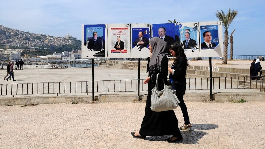 Women walk past electoral posters in Algiers, Monday, April 14, 2014.  Six candidates are running for the powerful presidency in the April 17 elections. (AP Photo/Ouahab  Hebbat)