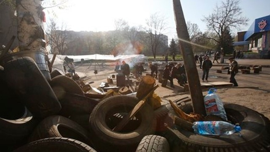 April 16, 2014: People gather in front of a barricade across a street in Slovyansk, eastern Ukraine. The city of Slovyansk has come under the increasing control of the pro-Russian gunmen who seized it last weekend.