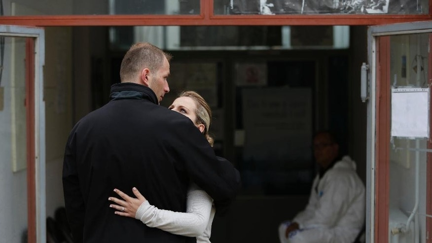 Bosnian woman Denisa Hegic hugs her husband as she enters at the  Sejkovaca identification center, near the Bosnian town of Sanski Most, 260 kilometers (162 miles) northwest of Sarajevo ,on Wednesday, April 16, 2014. Denisa Hegic was eight when Serb soldiers stormed her house and killed her entire family at the beginning of the 1992-95 Bosnian war. An aunt pulled her away from her mother's bloody body and they tried to run away, were caught but escaped again. After 22 years, Hegic reunited with her family on Wednesday at the freezing mortuary where the remains of hundreds of Muslim Bosniaks killed during the Bosnain Serb ethnic killings campaign are stored after they were excavated from Bosnia's biggest mass grave.(AP Photo/Amel Emric)