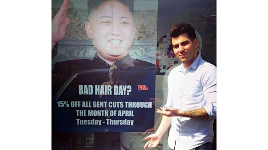 Karim Nabbach, son of the salon's owner, stands next to the poster that drew the wrath of North Korean officials (M&M Hair Academy)