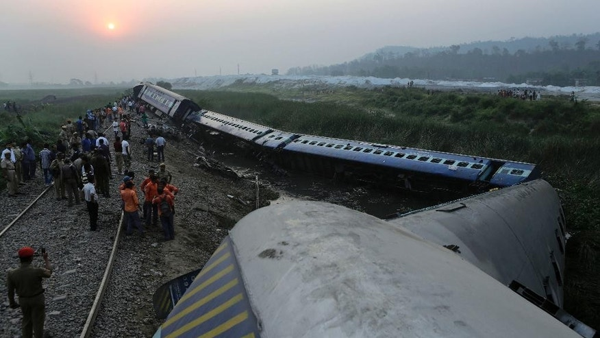 April 16, 2014: An Assam police officer, left, takes a photograph on his mobile of a train that derailed near Jagiroad Railway Station, about 56 miles east of Gauhati, India.