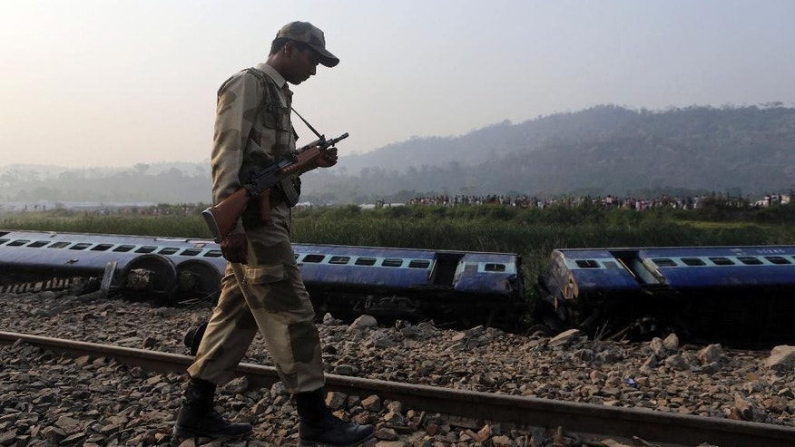 A security officer patrols past a train that derailed near Jagiroad Railway Station, about 90 kilometers (56 miles) east of Gauhati, India, Wednesday, April 16, 2014. According to a Northeast Frontier Railway officer, dozens of people were injured when the train jumped the tracks and derailed early Wednesday. (AP Photo/Anupam Nath)