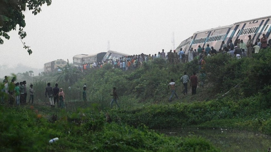 Locals and others gather around a train that derailed near Jagiroad Railway Station, about 90 kilometers (56 miles) east of Gauhati, India, Wednesday, April 16, 2014. According to a Northeast Frontier Railway officer, dozens of people were injured when the train jumped the tracks and derailed early Wednesday. (AP Photo/Anupam Nath)